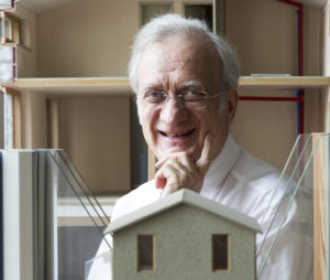 Dr. Wolfgang Feist smiling behind a model Passive House window frame