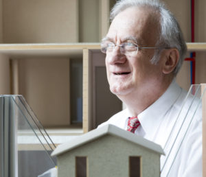 Dr. Wolfgang Feist sitting behind Passive House window models