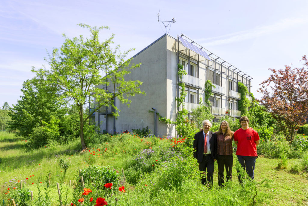 Dr. Wolfgang Feist and his familz standing outside the first Passive House on a sunny day