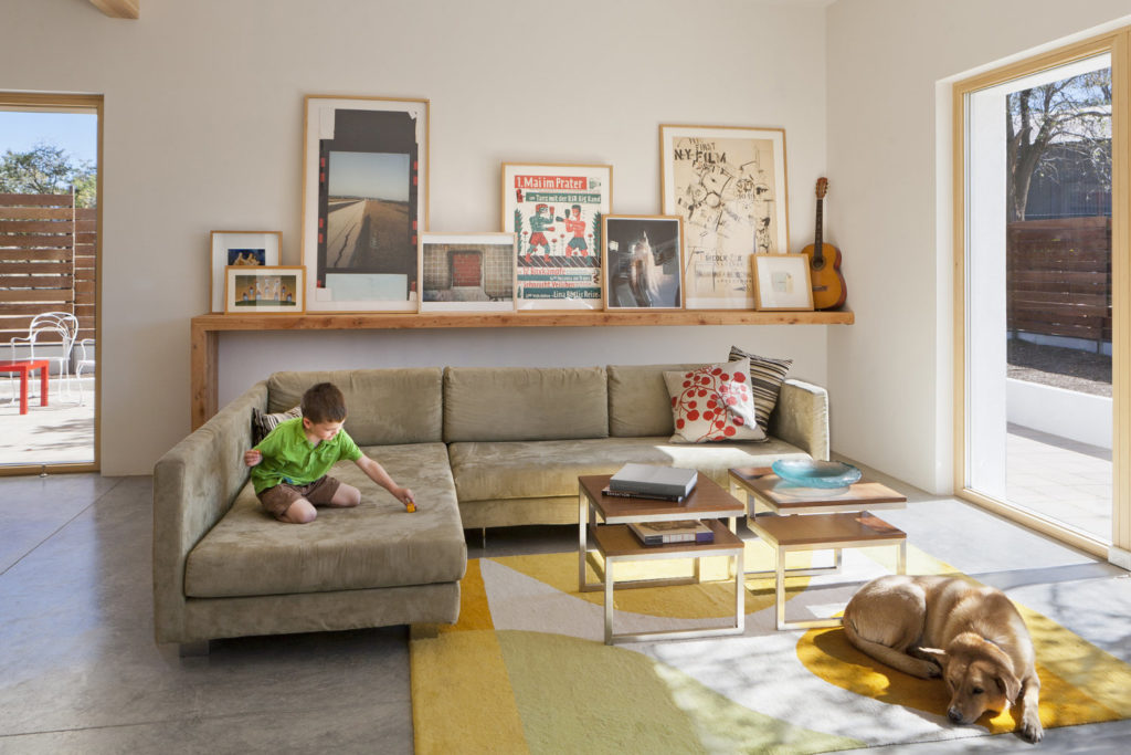 A comfortable living room with a boy playing on the couch and a dog relaxing on a rug