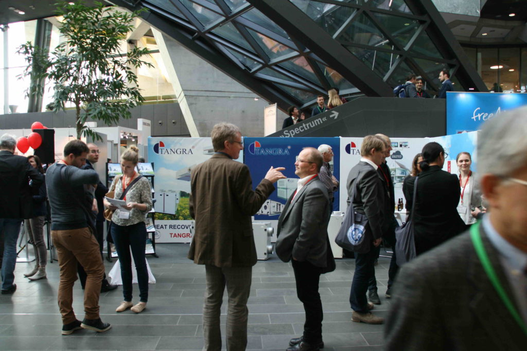 People discuss Passive House with each other in the exhibition area of the Passive House Conference