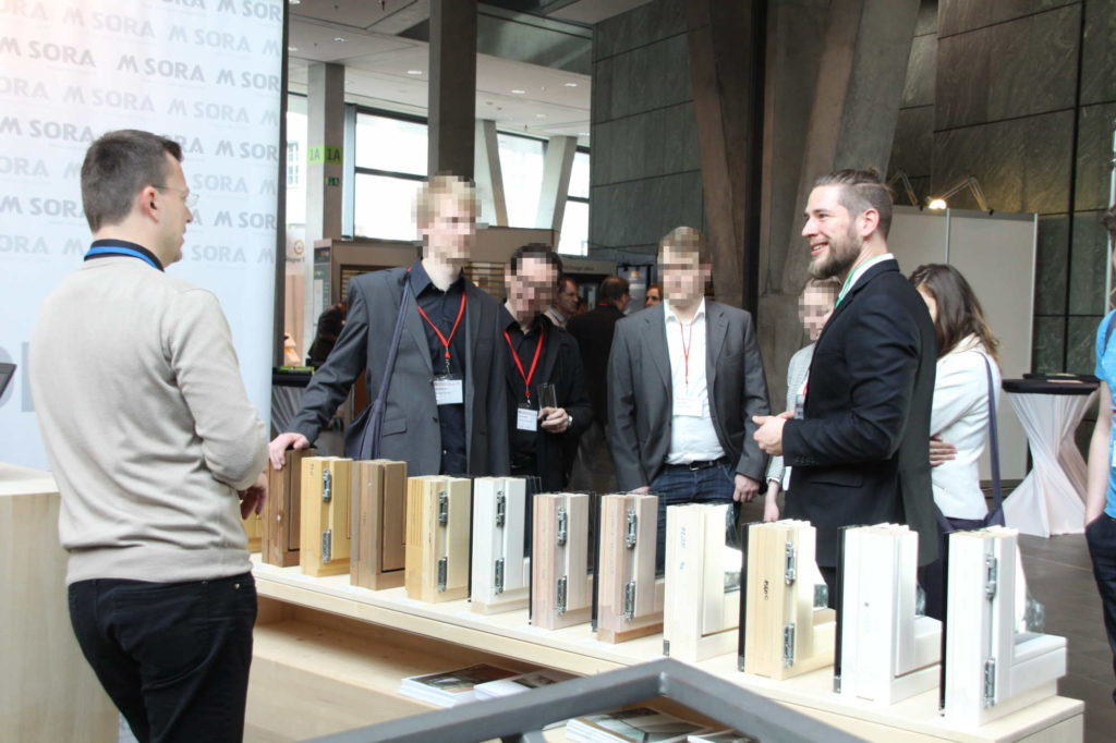 A scientist from Passive House Institute introudces conference participants to a window manufacturer with several examples of windows on display