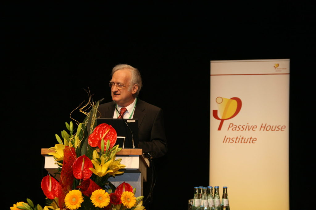 Wolfgang Feist, director of Passive House Institute speaking behind a bouquet of flowers with the Passive House Institute logo in the background ©PHI