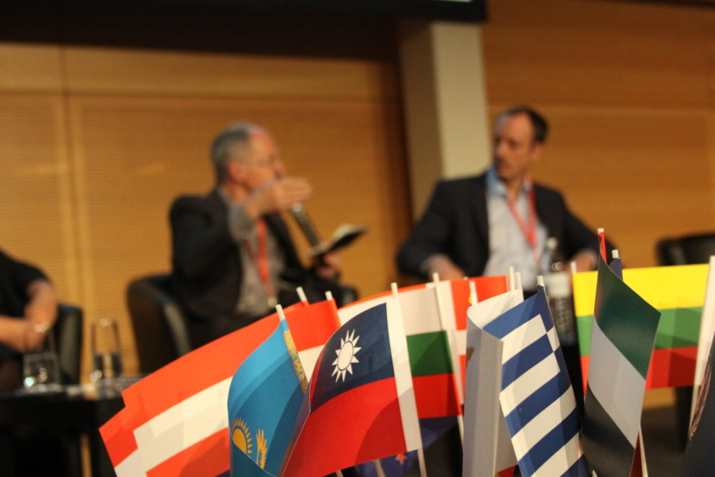 Flags from various countries with blurred key note speakers in the background