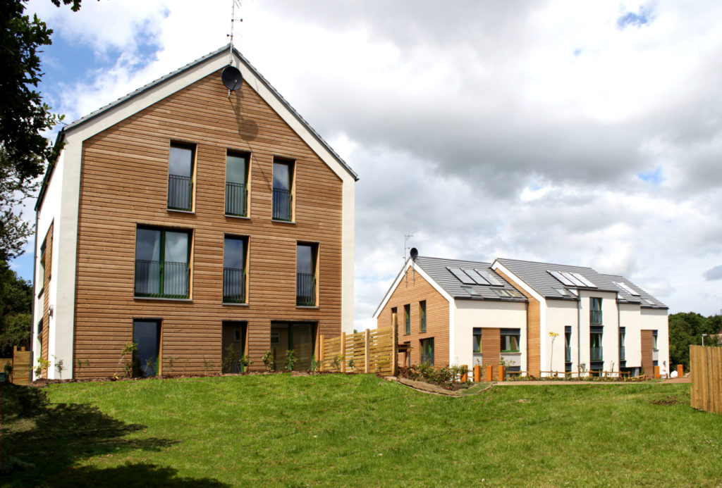 Several large multi-unit Passive House dwellings with lawns, pictured on a sunny day with clouds