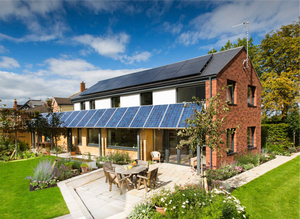 A Passive House building on a summers day with solar panels oriented towards the south