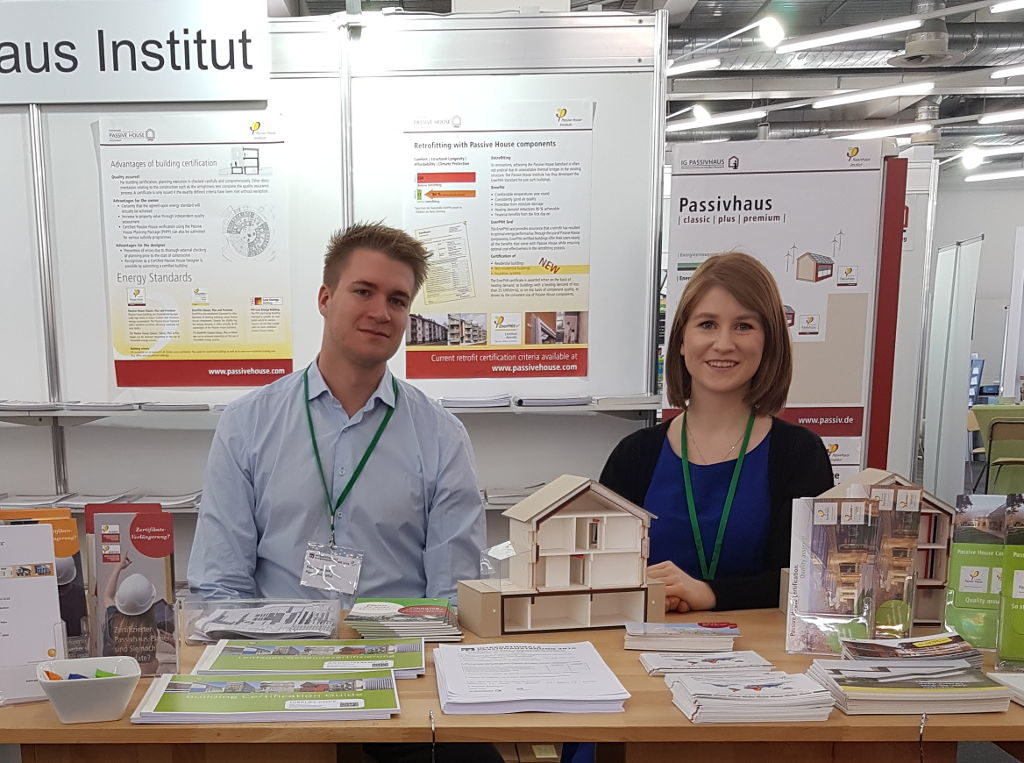 Two employees of iPHA sitting at a desk with posters, information leaflets detailing how Passive House works