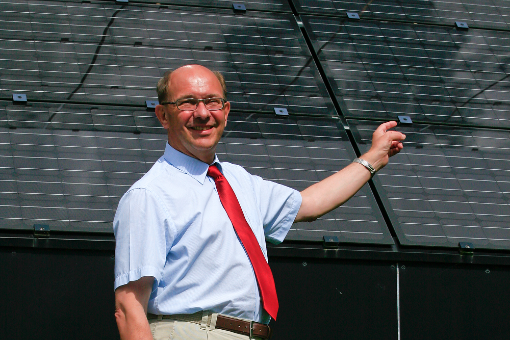 Headshot of a Mr. Torben Esbensen standing in front of an array of solar panels
