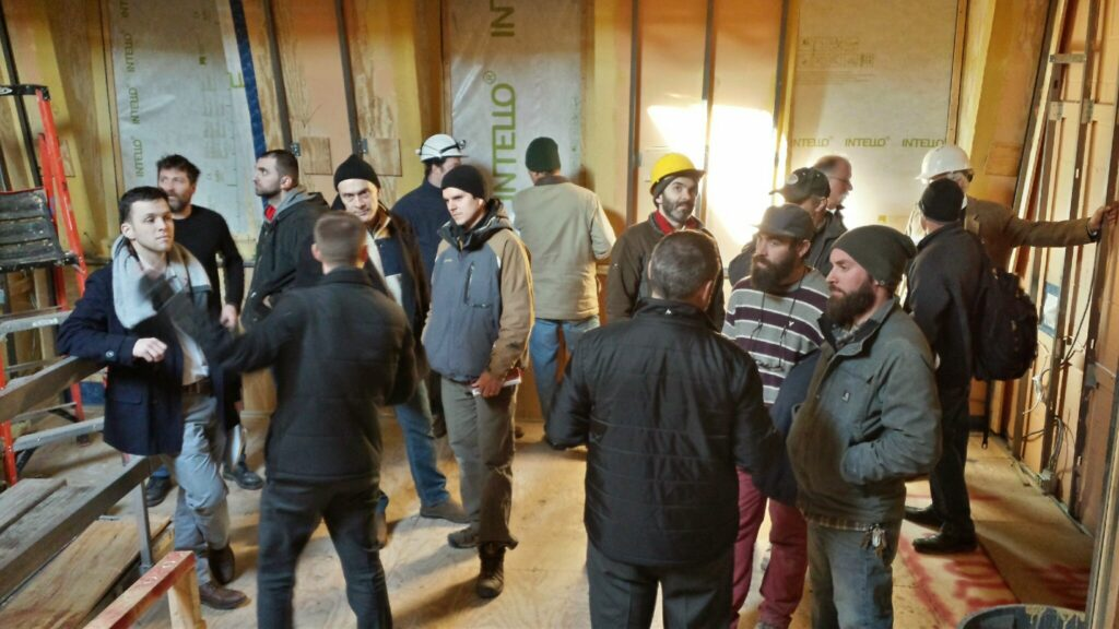 Builders, architects, clients, and other interested parties chatting at a Passive House construction site
