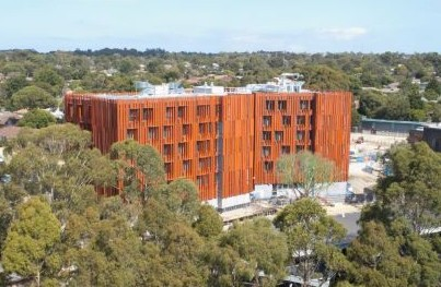 View of the entire Monas Gillies Hall Passive House Project. Distinguishable by its bright orange color.